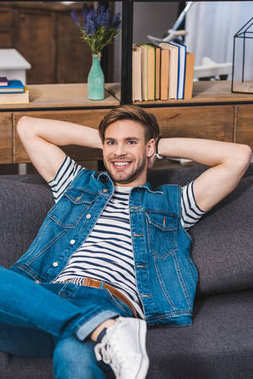 handsome young man sitting on sofa and smiling at camera
