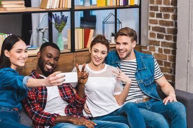 cheerful young multiethnic friends taking selfie with smartphone while sitting on sofa