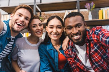 happy young multiethnic friends smiling at camera