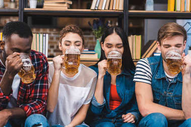 young multiethnic friends sitting together and drinking beer