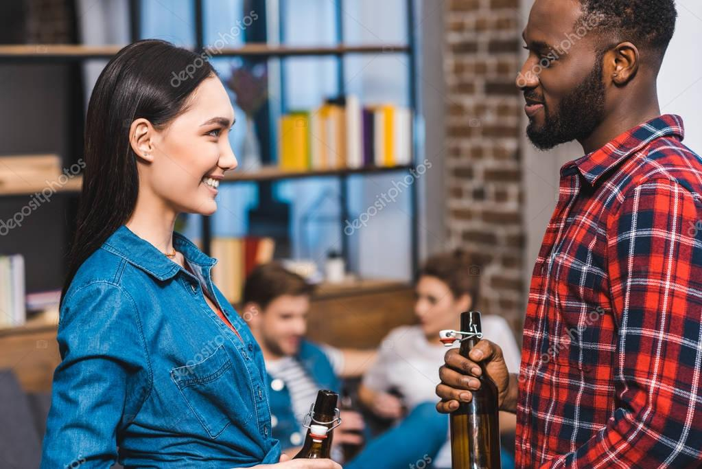 young multiethnic couple holding bottles of beer and looking at each other while friends sitting behind