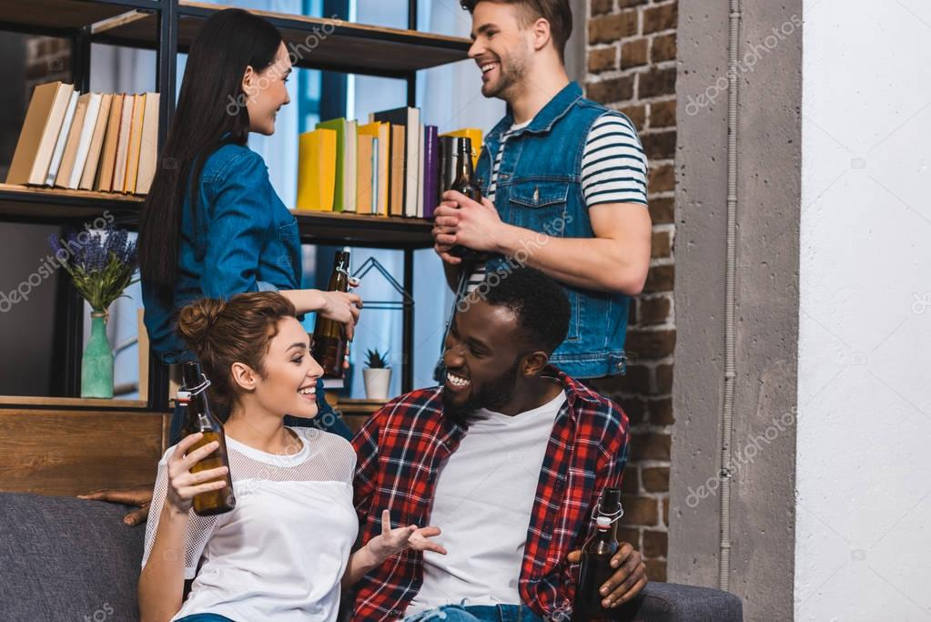 happy young multiethnic friends drinking beer and talking at home
