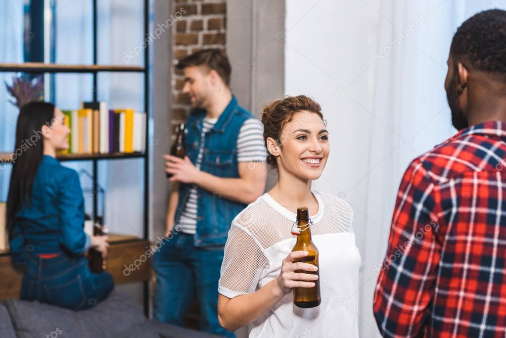 smiling young multiethnic friends drinking beer and talking at home
