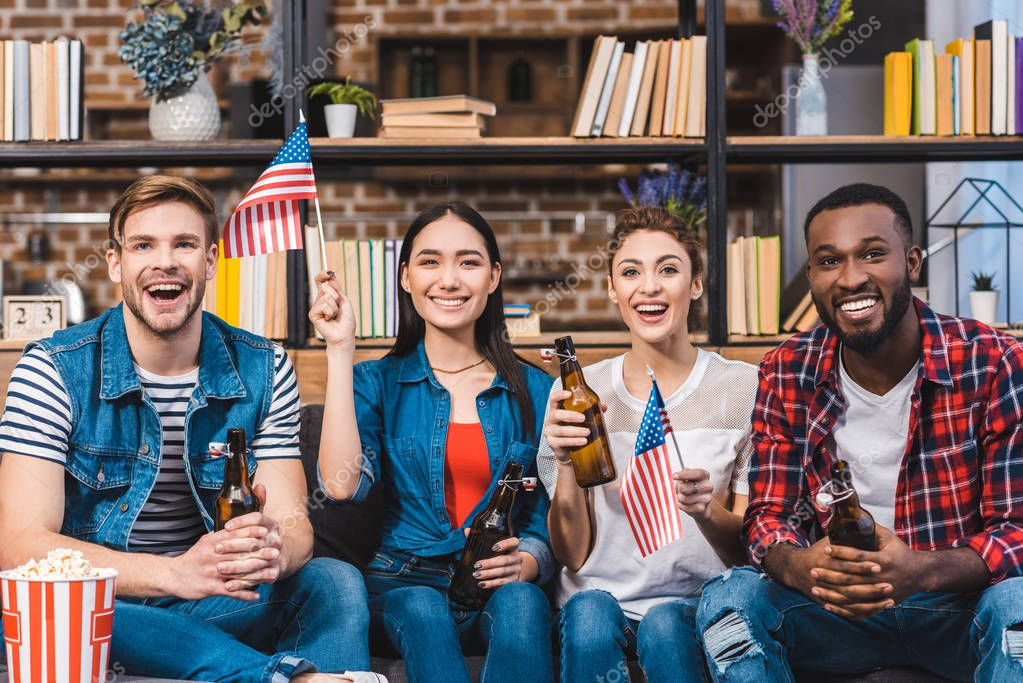 happy young multiethnic friends holding american flags and drinking beer at home