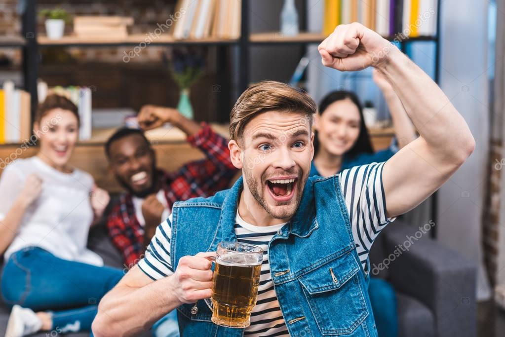 excited young man holding glass of beer and watching tv with friends sitting behind