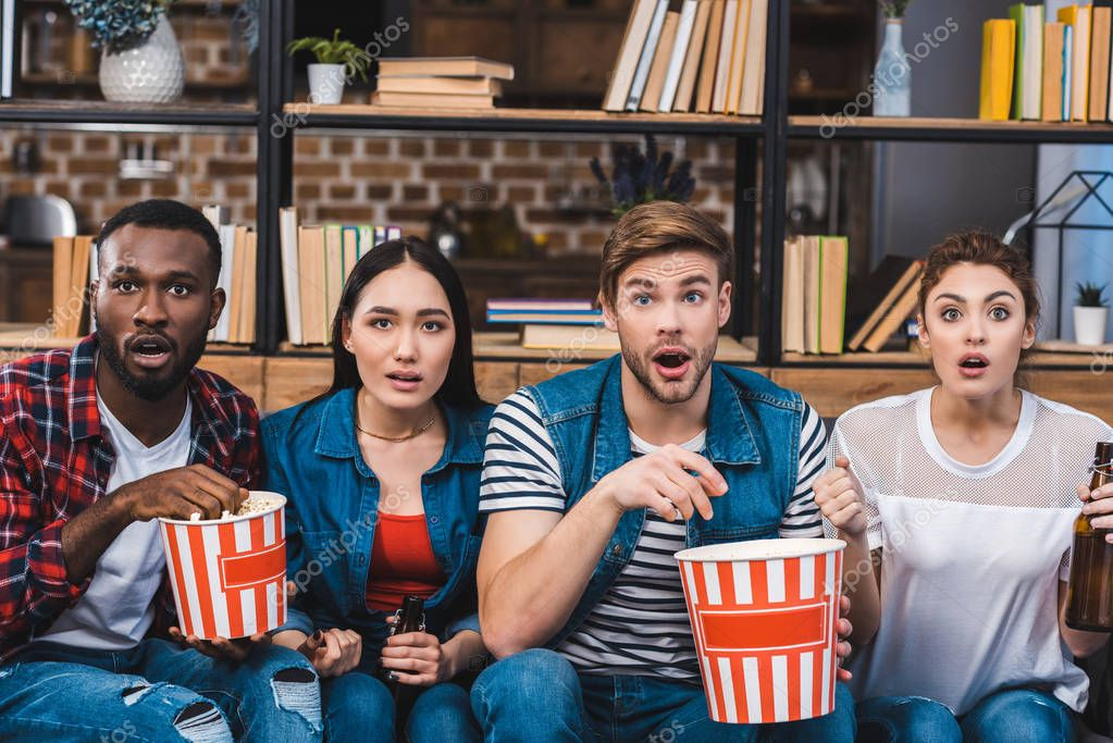 shocked young multiethnic friends eating popcorn and drinking beer while watching tv