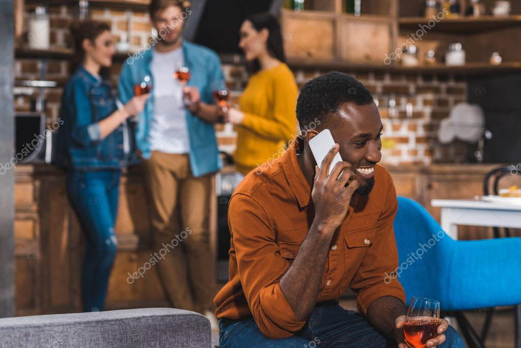 happy young african american man talking by smartphone while friends drinking wine behind