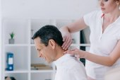 boční pohled masérka dělá sedící masáž šíje pro klienta v kanceláři