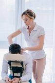 atraktivní masérka dělá ramena masáž na sedadle v kanceláři