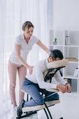 masérka dělá masáž zad pro podnikatele v kanceláři