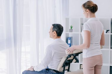 businessman sitting on massage chair with masseuse behind him at office