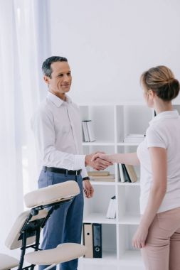 businessman shaking hand of masseuse at office