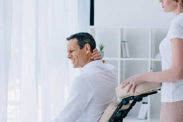 businessman with pain in neck sitting in masseuse office