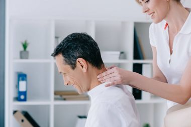 side view of masseuse doing seated neck massage for client at office