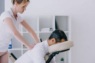 side view of masseuse doing seated massage for businessman
