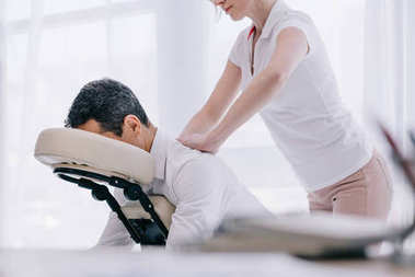 masseuse doing seated back massage for businessman at office