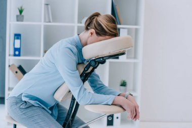 businesswoman sitting on massage chair at office