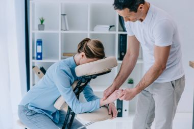 masseur doing hands massage for businesswoman at office
