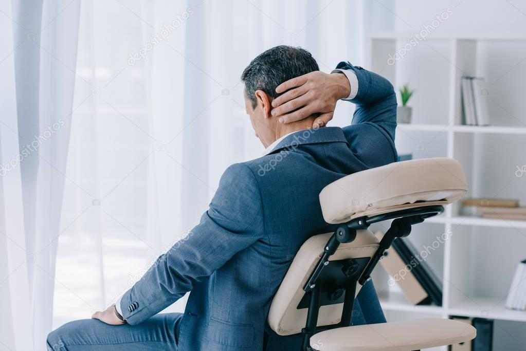 adult businessman with painful backache sitting in massage chair at office