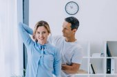 trainer learning beautiful businesswoman how to stretch at office