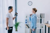 side view of businesswoman and her personal trainer working out with dumbbells at office