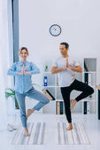 fit businesswoman with her trainer practicing yoga in tree pose at office