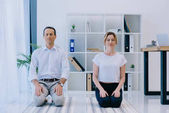 handsome businessman with his trainer meditating on yoga mats at office