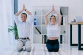 mature businessman with his trainer meditating on yoga mats at office