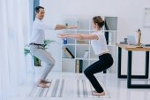 side view of businessman with his trainer practicing yoga in Awkward pose at office