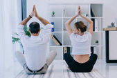 businessman with his trainer practicing yoga in Lotus pose at office