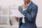 oříznuté záběr promyšlené podnikatel čtení obchodní papíru v kanceláři
