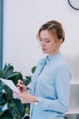 Fotografie attractive businesswoman with pencil reading document