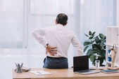 Photo rear view of mature businessman with backache at office