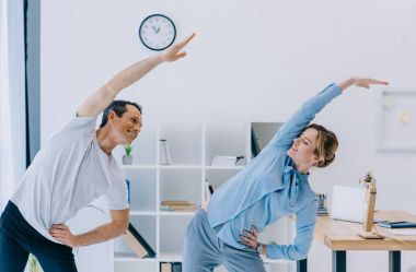 businesswoman doing side bend with trainer at office