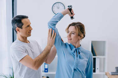 businesswoman and her mature personal trainer doing exercise with dumbbell at office
