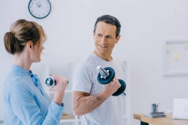 businesswoman and her handsome mature personal trainer working out with dumbbells at office