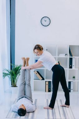 businessman with his trainer practicing yoga in ssss pose at office