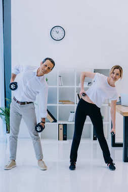 mature businessman with his female personal trainer working out with dumbbells at office