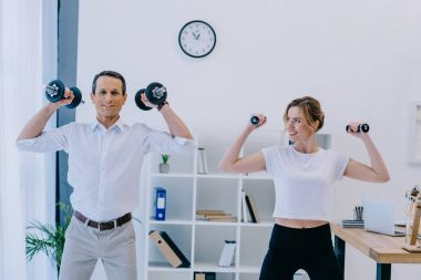 businessman with his beautiful personal trainer working out with dumbbells at office