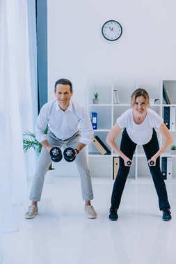 handsome businessman with his female personal trainer working out with dumbbells at office