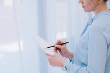 cropped shot of businesswoman with pencil reading document