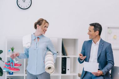 attractive businesswoman with fitness equipment talking with colleague at office