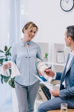 businesswoman with fitness equipment talking with colleague at office