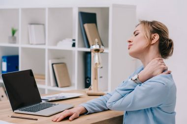 businesswoman with neckpain sitting at workplace in office