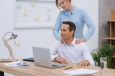 businessman working with laptop at workplace while woman doing massage for him