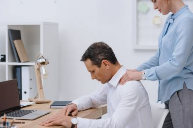 businessman working with laptop at workplace while his colleague doing massage for him