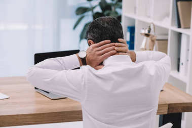 rear view of businessman with neck pain at workplace in office