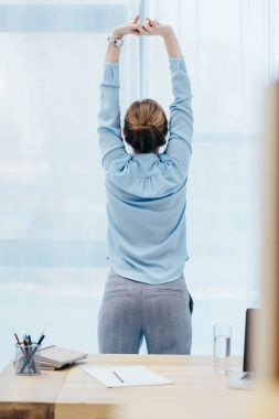 rear view of businesswoman stretching at office
