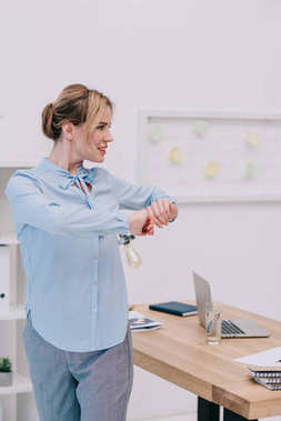 attractive businesswoman doing physical jerks at workplace