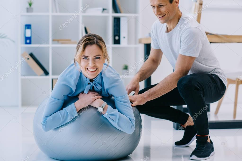 businesswoman working out on fit ball with trainer at office